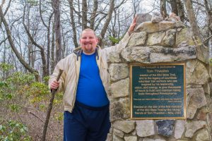 portrait of man in front of plaque in the woods
